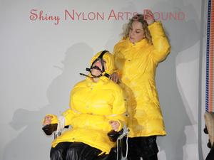Nongrid_medium_watching-sandra-being-tied-and-gagged-with-ropes-and-a-holster-from-sophie-both-wearing-sexy-black-shiny-nylon-pants-and-yellow-down-jackets-pics