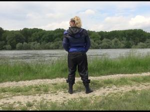 Nongrid_medium_watching-sexy-sophie-wearing-a-supersexy-black-rain-pants-with-rubber-boots-and-a-blueblack-down-jacket-walking-on-a-riverside-video